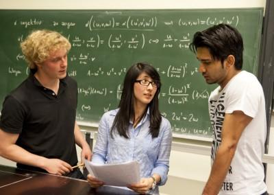 Drei Studenten diskutieren nach der Mathematik-Vorlesung vor einer Tafel mit Formeln in einem Hörsaal des Geomatikums der Universität Hamburg