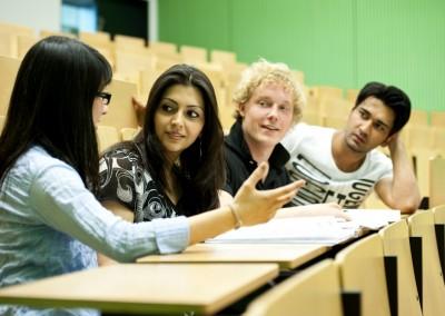 Studenten diskutieren im Hörsaal nach der Vorlesung