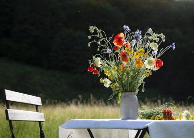 """Tisch mit Sommerblumenstrauss vor der ehemaligen Gaststätte """"Eisenhammer"""" in Bockschmiede"""